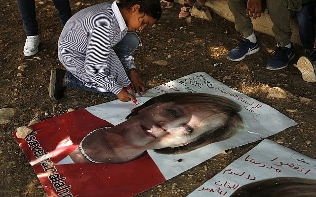 """A Bedouin child writes on a picture of German Chancellor Angela Merkel ahead of her expected visit to Israel on Wednesday, in the West Bank Bedouin community of Khan al-Ahmar, Oct. 2, 2018. Arabic on the poster reads, """"save Khan al-Ahmar"""" and """"save our school."""" (AP Photo/Nasser Shiyoukhi)"""
