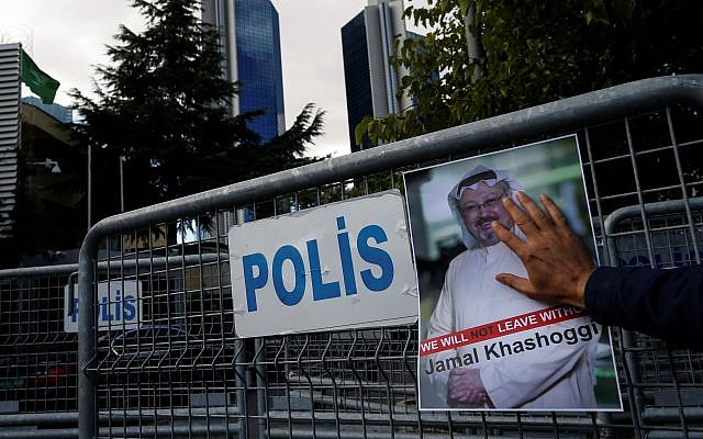 A man places a poster of missing Saudi writer Jamal Khashoggi, on a barrier that blocks the road leading to the Saudi Arabia consulate in Istanbul, as people gather in his support,Friday, Oct. 5, 2018. (AP/Emrah Gurel)