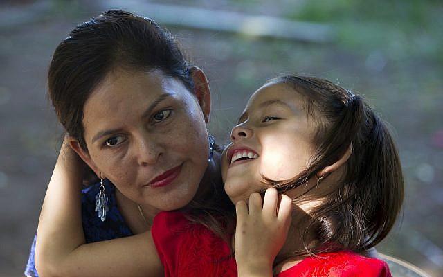 Araceli Ramos holds her 5-year-old daughter, Alexa, on her lap during an interview in a park in San Miguel, El Salvador, on August 18, 2018. (AP Photo/Rebecca Blackwell)