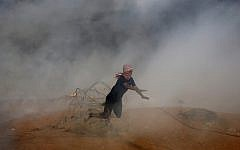 A protester falls down on barbed fence as he runs for cover from tear gas fired by Israeli troops while others burn tires near the Gaza Strip's border with Israel during a protest east of Khan Younis, southern Gaza Strip, Friday, Oct. 5, 2018 (AP Photo/Adel Hana)