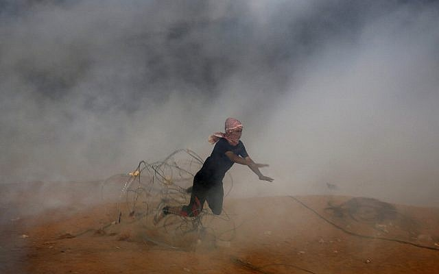 Illustrative. A protester falls down on barbed fence as he runs for cover from tear gas fired by Israeli troops while others burn tires near the Gaza Strip's border with Israel during a protest east of Khan Younis, southern Gaza Strip, Friday, Oct. 5, 2018 (AP Photo/Adel Hana)