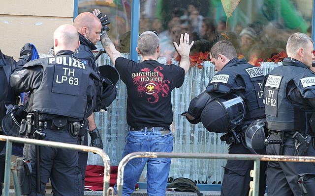 In this October 6, 2018 photo police officers search a visitor of a far right rock concert in Aploda, Germany. Slogan on the shirt reads 'guaranteed indexed'. (Sebastian Haak/dpa via AP)