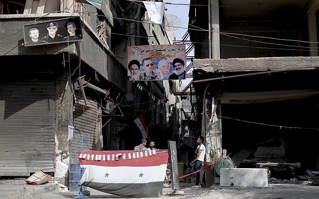Men sit under a poster of the late Iranian revolutionary founder Ayatollah Khomeini, left, Syrian President Bashar Assad, second left, Head of the Popular Front for the Liberation of Palestine-General Command Ahmed Jibril, second right, and Hezbollah leader Sayyed Hassan Nasrallah at a check point in the Palestinian refugee camp of Yarmouk in the Syrian capital Damascus, Syria, Saturday, Oct. 6, 2018 (AP Photo/Hassan Ammar)