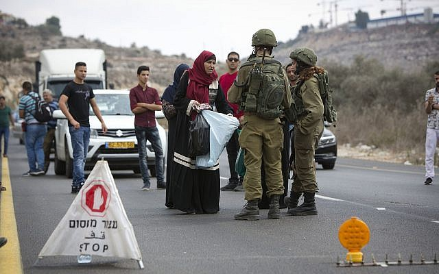 Palestinians wait at an Israeli checkpoint near the scene of a shooting attack at Barkan Industrial Zone in the northern West Bank on October 7, 2018. (AP Photo/Majdi Mohammed)