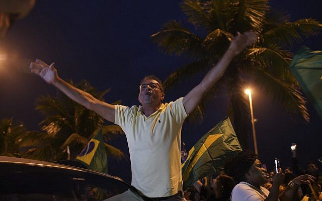 A supporter of Jair Bolsonaro, presidential candidate with the Social Liberal Party, celebrates in front of his house during the general elections in Rio de Janeiro, Brazil, Sunday, Oct. 7, 2018. (AP Photo/Ricardo Borges)
