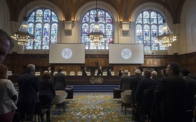 In this Wednesday Oct. 3, 2018, image The delegations of the US, front left, and the Islamic Republic of Iran, front right, rise as judges, rear, enter the International Court of Justice, or World Court, in The Hague, Netherlands.(AP/Peter Dejong)