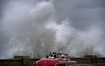 Waves crash against the Malecon, triggered by the outer bands of Hurricane Michael, as tourists drive past in a classic American car in Havana, Cuba, October 9, 2018. (AP Photo/Ramon Espinosa)