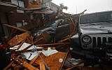 A storm chaser climbs into his vehicle during the eye of Hurricane Michael to retrieve equipment after a hotel canopy collapsed in Panama City Beach, Fla., Wednesday, Oct. 10, 2018. (AP Photo/Gerald Herbert)