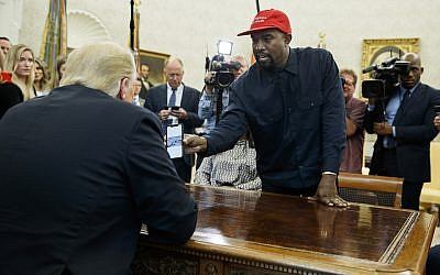 Rapper Kanye West shows President Donald Trump a photograph of a hydrogen plane during a meeting in the Oval Office of the White House October 11, 2018, in Washington. (AP Photo/Evan Vucci)
