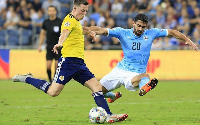 Scotland's Callum McGregor  (L) shoots by Israel's Omri Ben Harush during Nations League game in Haifa, Israel, Thursday, Oct. 11, 2018. (AP Photo/Ariel Schalit)