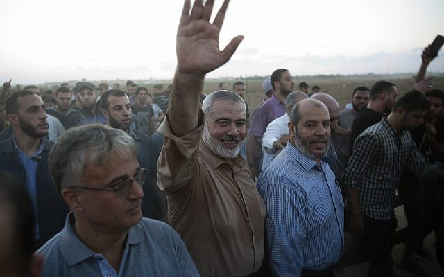 Palestinian Hamas top leader Ismail Haniyeh waves to protesters during a protest at the Gaza Strip's border with Israel, October 12, 2018. (AP Photo/Khalil Hamra)