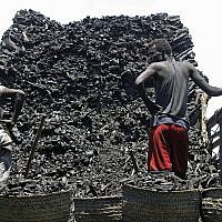 In this Tuesday Oct. 30, 2012 File photo, Somali porters offload charcoal from a truck at a charcoal market in Mogadishu, Somali (AP Photo/Farah Abdi Warsameh)