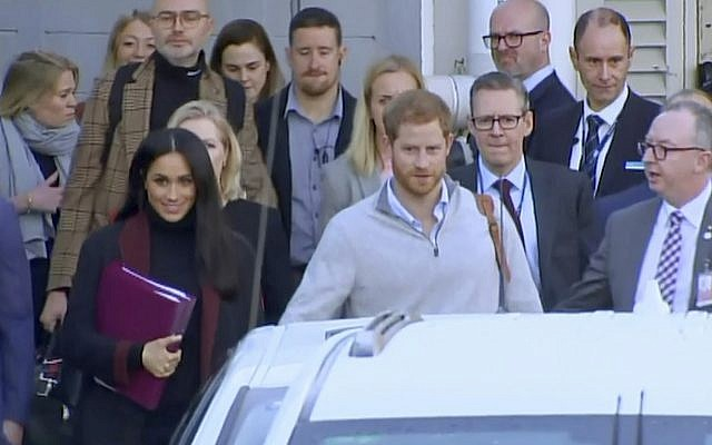 In this image made from video, Britain's Prince Harry, center right, and his wife Meghan Markle, left, Duke and Duchess of Sussex, approach a car at an airport in Sydney, October 15, 2018 (Australian Pool via AP)