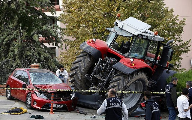 Forensic officers work at the scene after a tractor crashed into cars outside a residence, in Ankara, Turkey, Oct. 16, 2018 (AP Photo/Burhan Ozbilici)