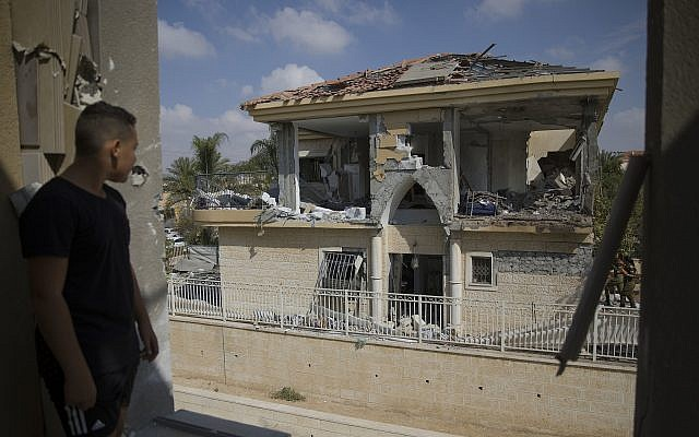 A man watches a house that was hit by a missile fired from Gaza Strip, in the city of Beersheba, southern Israel, Wednesday, Oct. 17, 2018. (AP/Tsafrir Abayov)