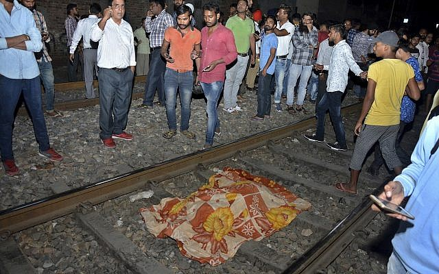 The body of a victim of a train accident lies covered in cloth on a railway track in Amritsar, India, Oct. 19, 2018 (AP Photo/Prabhjot Gill)
