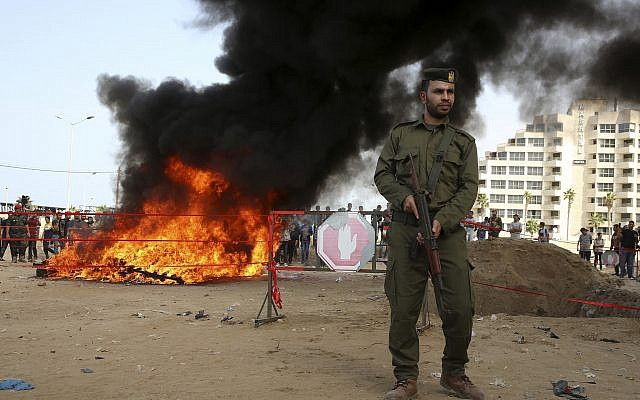 Hamas security forces stand guard while they burn some 1,383 bars of hashish and 1,242,000 pills of Tramadol, that have been seized since the beginning of the year, in Gaza City, Oct. 22, 2018. (AP Photo/Adel Hana)