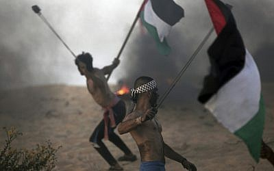 Palestinian protesters hurl stones at Israeli troops during a protest on the beach at the border with Israel near Beit Lahiya, northern Gaza Strip, Oct. 22, 2018. (AP Photo/Khalil Hamra)