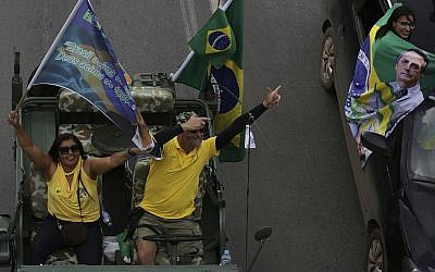 Making a gun sign with their hands, supporters parade in their cars during a rally in support of right-wing presidential candidate Jair Bolsonaro, in Brasilia, Brazil, October 27, 2018 (AP Photo/Eraldo Peres)