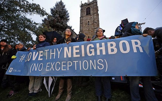 A group holds a sign in Squirrel Hill, Pittsburgh during a memorial vigil for the victims of the shooting at the Tree of Life Synagogue on October 27, 2018. (AP Photo/Gene J. Puskar)