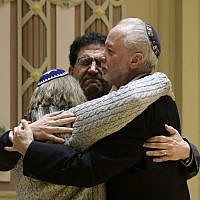 Rabbi Jeffrey Myers, right, of Tree of Life/Or LSimcha Congregation hugs Rabbi Cheryl Klein, left, of Dor Hadash Congregation and Rabbi Jonathan Perlman during a community gathering held in the aftermath of a deadly shooting at the Tree of Life Synagogue in Pittsburgh, Oct. 28, 2018. (AP Photo/Matt Rourke)