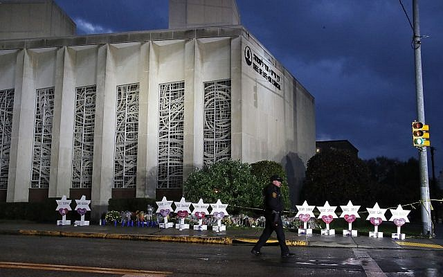 Tree of Life Synagogue with memorial Stars of David; night shot; policeman walks by