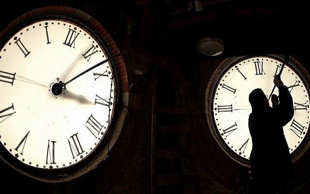 Illustrative: A custodian inspects a clock face before changing the time on the 100-year-old clock in Clay Center, Kansas on March 8, 2014. (AP Photo/Charlie Riedel)