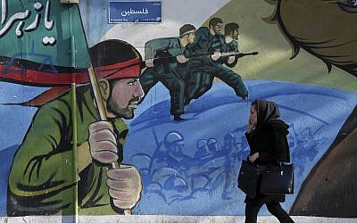 An Iranian woman walks past a mural depicting Iranian armed forces in the battlefield, at Palestine Sq. in Tehran, Iran, Saturday, January 16, 2016. (AP Photo/Vahid Salemi)