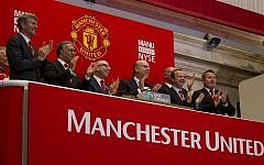 Executives from Manchester United, including Avram Glazer, fourth from left, and Joel Glazer, third from left, applaud after ringing the opening bell at the New York Stock Exchange on Friday, Aug. 10, 2012 in New York. (AP/Jin Lee)