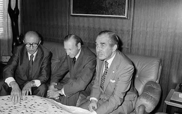 Israeli Prime Minister Menachem Begin, left, points to spot on Israeli map spread over a table at United Nations office of Secretary-General Kurt Waldheim Friday, July 22, 1977. At right is U.N. Ambassador Chaim Herzog. (AP Photo/Marty Lederhandler)