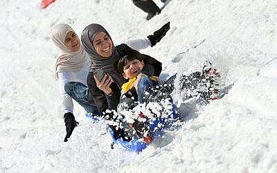 Tourists from Saudi Arabia enjoy a ride on a bob sled on the glacier of the Kitzsteinhorn mountain in Kaprun, in the Austrian province of Salzburg, Wednesday, June 10, 2015. (AP Photo/ Kerstin Joensson)