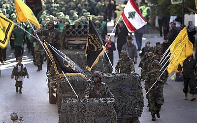 Hezbollah fighters stand on their armed vehicles and hold their party flags, as they parade during a rally to mark the 13th day of Ashoura, in the southern market town of Nabatiyeh, Lebanon, November 7, 2014 (AP Photo/Mohammed Zaatari)