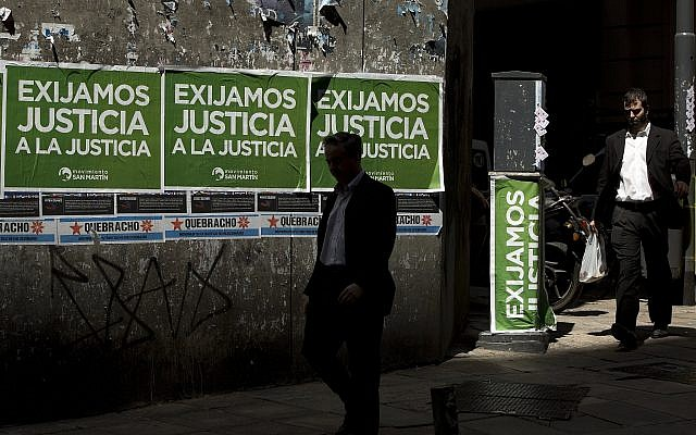 "Men walk pass posters that read in Spanish ""Demand justice to justice,"" in reference to march organized by federal prosecutors demanding justice after the death of special prosecutor Alberto Nisman, in Buenos Aires, Argentina, February 13, 2015. (AP Photo/ Rodrigo Abd/ File)"