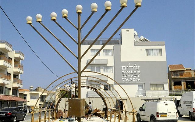 Construction workers build the frame of a World War II-era Quonset hut in front of the Jewish Community Center in Larnaca, Cyprus. (Larry Luxner/ Times of Israel)