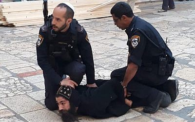 Israel Police officers restrain a Coptic cleric during a protest against safety maintenance work at the Church of the Holy Sepulchre in the Old City of Jerusalem, October 24, 2018. (Patriarchate of the Orthodox Copts in Jerusalem/Facebook)