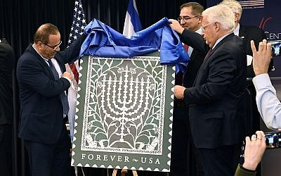 US Ambassador to Israel David Friedman, right, and Israel's Communications Minister Ayoub Kara unveil the Israel Post and US Postal Service joint stamp for Hanukkah at the American Center, Jerusalem, October 16, 2018. (Matty Stern/US Embassy Jerusalem)