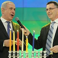 Prime Minister Benjamin Netanyahu (L) and then education minister Gideon Sa'ar light candles to celebrate the Jewish holiday of Hanukkah during the Bible Quiz at the International Conference Center in Jerusalem, on December 12, 2012. (Miriam Alster/Flash90)