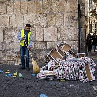 A municipality worker cleans garbage off the ground in the Muslim quarters of Jerusalem's Old City on March 4, 2016. (Corinna Kern/Flash90)