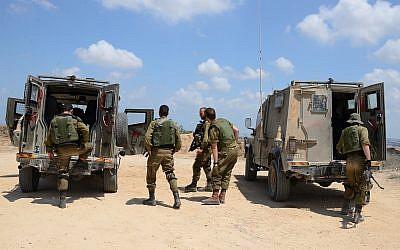 Israeli soldiers boarding armored vehicles on their way to patrol along the Israeli-Gazan border on July 21, 2018. (Gili Yaari/FLASH90)