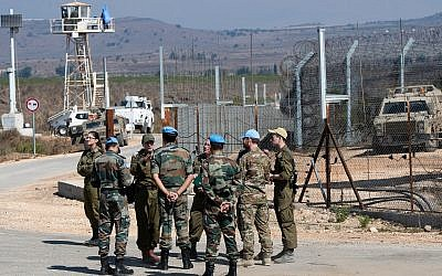 UN peacekeepers and Israeli soldiers are seen on the Israeli side of the Quneitra Crossing between Israel and Syria in the Golan Heights on September 27, 2018. (Basel Awidat/Flash90)