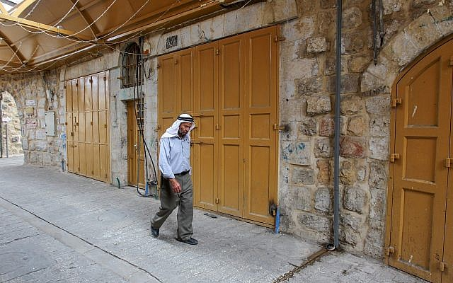 A Palestinian man walks past closed shops in the Old City of Hebron, due to a general strike in response to Israel's Nation State Law on October 1, 2018 (Wisam Hashlamoun/Flash90)