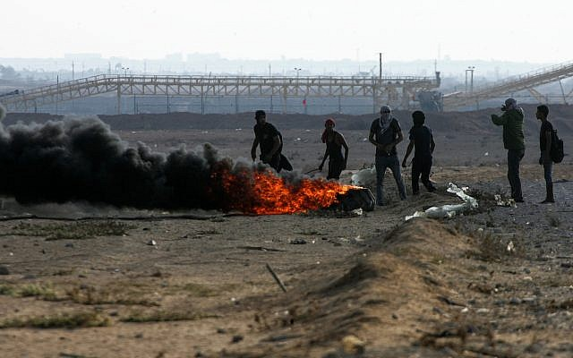 """Palestinian demonstrators burn tires as they demonstrate during the """"Great March of Return"""" on the Gaza-Israel border in Rafah, Gaza on October 12, 2018. (Abed Rahim Khatib/Flash90)"""