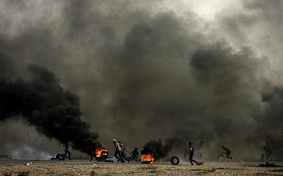 """Palestinians burn tires as they demonstrate during the """"Great March of Return"""" on the Gaza-Israel border in Rafah, Gaza on October 12, 2018. (Abed Rahim Khatib/Flash90)"""