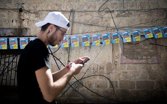 A man stands near posters of Jerusalem mayoral candidate Yossi Deitch outside the Mahane Yehuda market in Jerusalem on October 29, 2018, (Yonatan Sindel/Flash90)