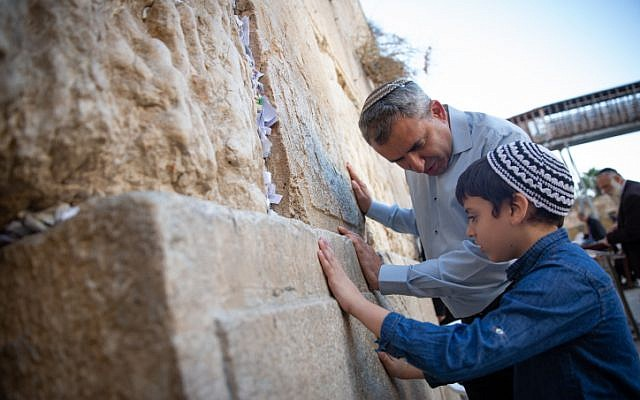Jerusalem mayoral candidate Ze'ev Elkin and his son pray at the Western Wall, in Jerusalem Old City, on the morning of the municipal elections on October 30, 2018. (Aharon Krohn/Flash90)