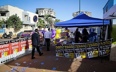 Campaign activists outside a voting station on the morning of the municipal elections, in Ashdod, on October 30, 2018. (Flash90)