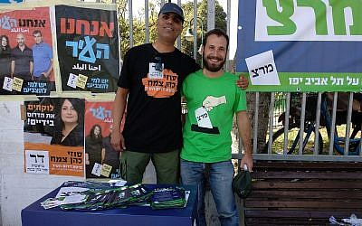 Sasi Ben Menachem, left, of Suzy Cohen-Zemach's South of the City party, and Nir Simon of Meretz shared a table outside a polling station in the Shapira neighborhood of Tel Aviv during local elections on October 30, 2018. (Melanie Lidman/Times of Israel)