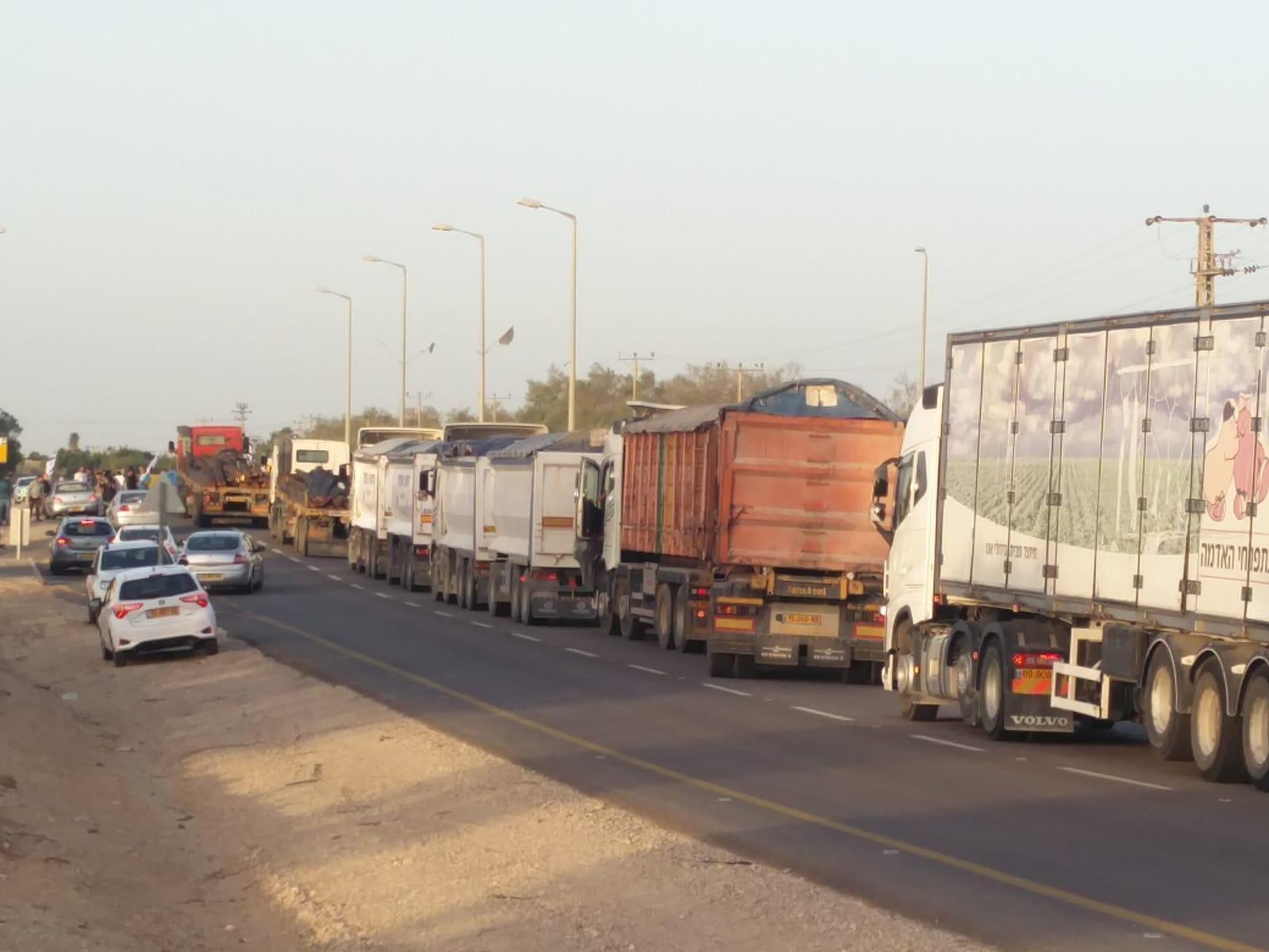 Residents from the south and activists from the right-wing Im Tirtzu organization block trucks entering Gaza through the Kerem Shalom Crossing