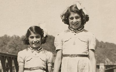 Sisters Gita and Zuzana Hojtasova in Prague after liberation from Terezin in 1945. Their clothes do not fit — their dresses are short, and their shoes are cut. (Courtesy Museum of Jewish Heritage)