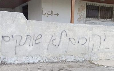 Hebrew graffiti reading 'Jews are not silent' found sprayed on the wall of a mosque in Palestinian West Bank village of Krayot, October 10, 2018. (Bashar Karioti,/Rabbis for Human Rights)